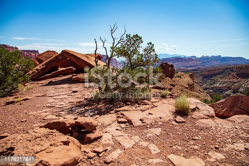 Large slabs of reddish sandstone balance atop each other in a geological artistic sculpture