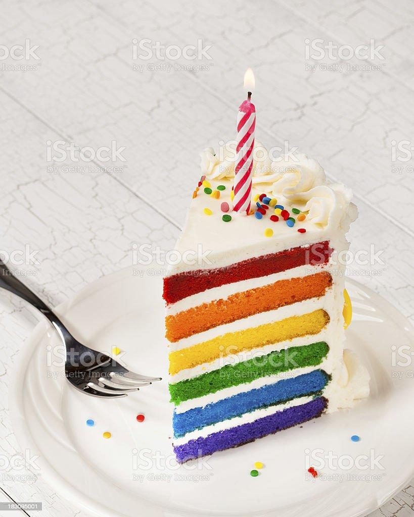 Large slice of birthday cake with six rainbow layers stock photo