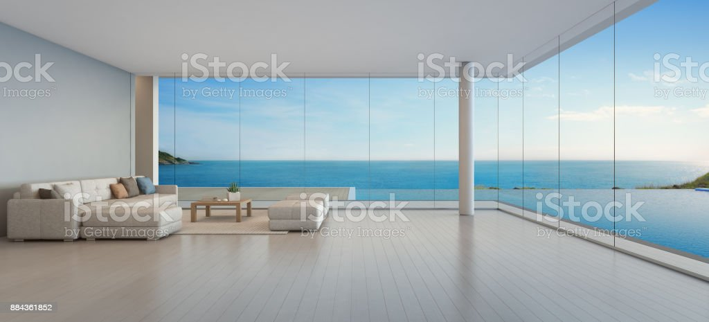 Large sofa on wooden floor near glass window and swimming pool with terrace at penthouse apartment, Lounge in sea view living room of modern luxury beach house or hotel stock photo