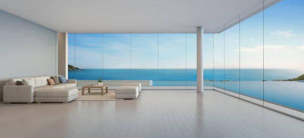 sofá grande en piso de madera cerca de la ventana de cristal y piscina con terraza en el ático, salón mar ve el salón de hotel o casa de playa de lujo moderno - mirar el paisaje fotografías e imágenes de stock