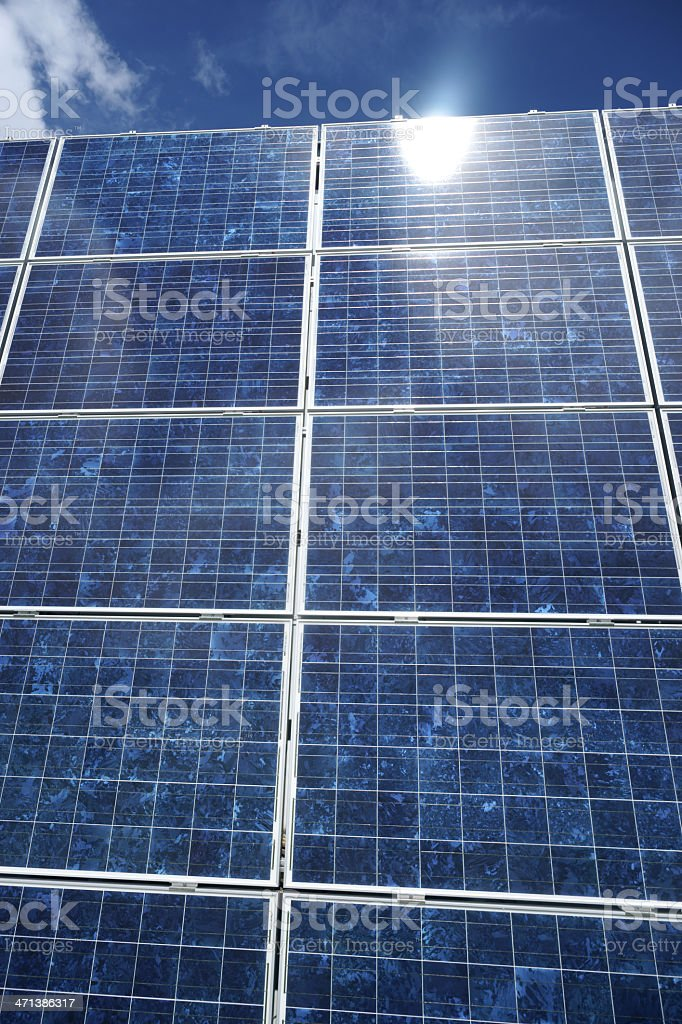 Large solar panel against sky with sun reflection - vertical royalty-free stock photo