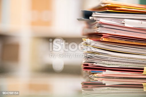 Large stack of file folders, documents, paperwork piled on glass top desk in office.  Bookshelves in background.