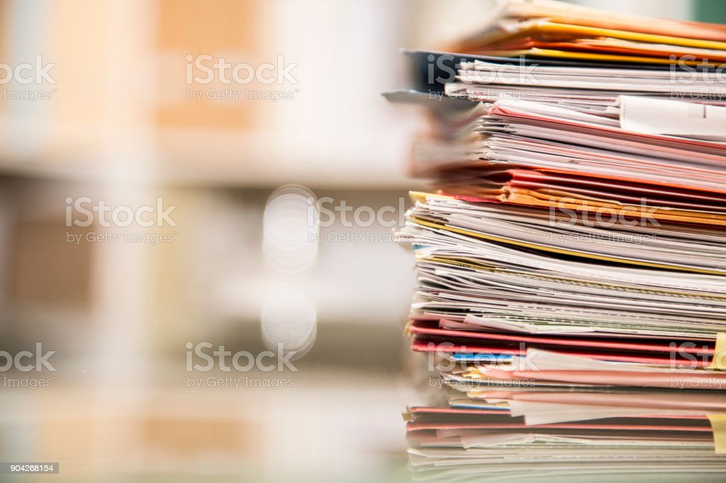 Large stack of files, documents, paperwork on desk. stock photo
