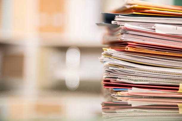 Large stack of files, documents, paperwork on desk. Large stack of file folders, documents, paperwork piled on glass top desk in office.  Bookshelves in background. document stock pictures, royalty-free photos & images