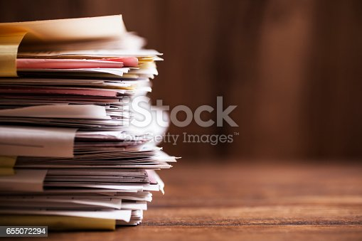 Large stack of files, paperwork on office desk with copyspace.  Overworked concept.
