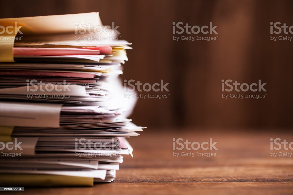 Large stack of paperwork, files on office desk with copyspace. stock photo
