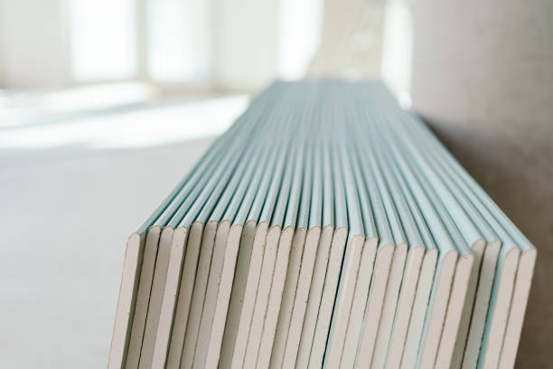 Large stack of white chip board against a wall stock photo
