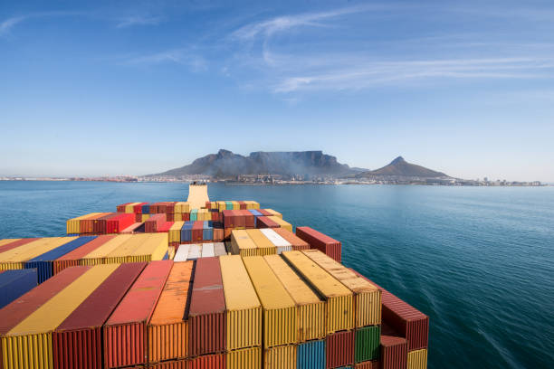 Large stacked container ship leaving the port of Cape Town with Table mountain and the city in the background, South Africa. stock photo