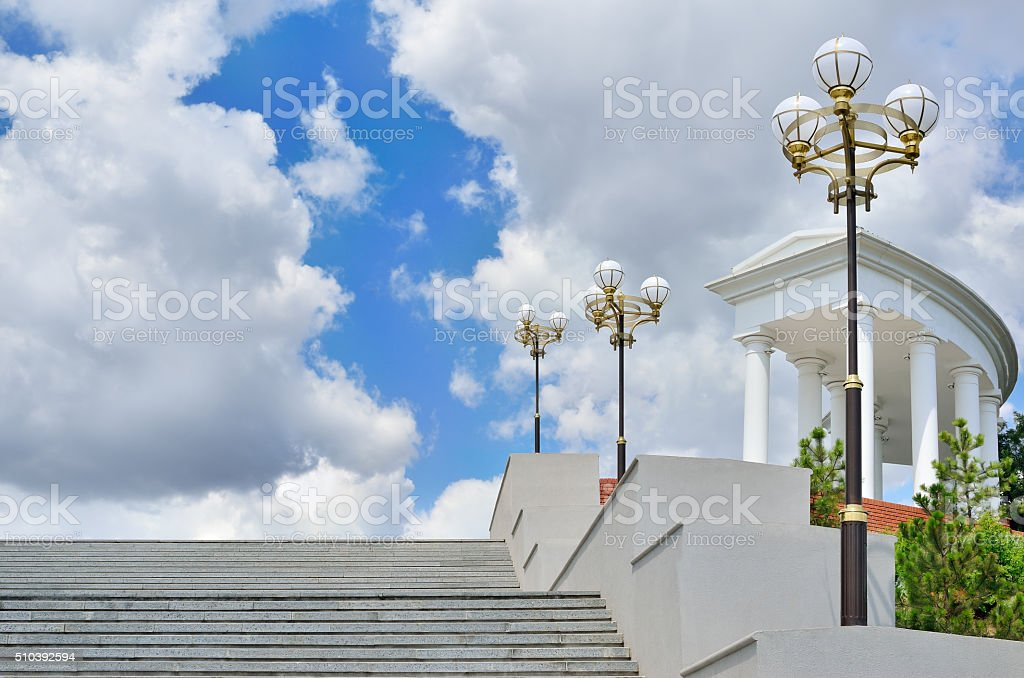 Large staircase with a colonnade on background of blue sky stock photo