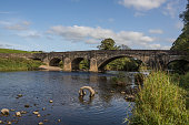 Old stone bridge in the ribble valley. Summer sky with white fluffy clouds