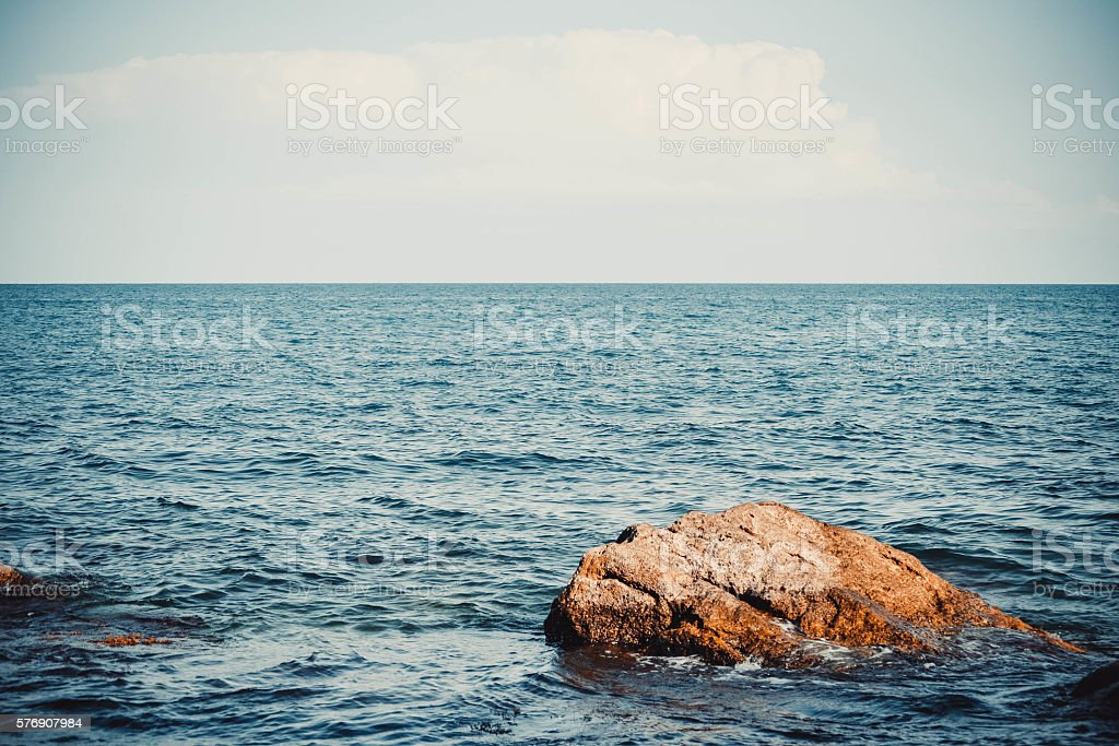 large  stone in the sea and skyline stock photo