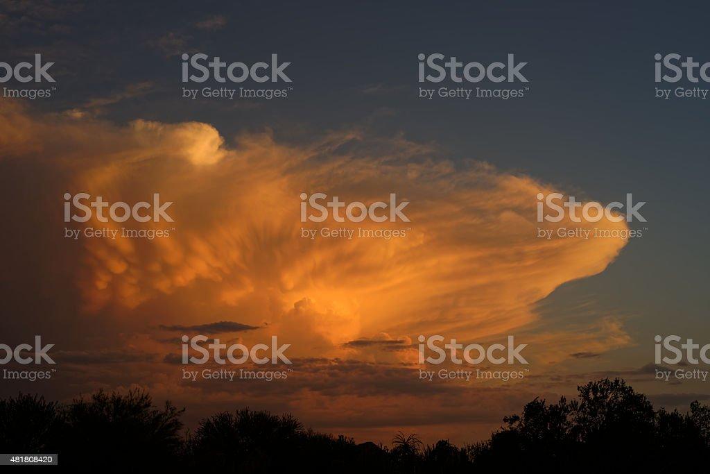 Large storm cloud at sunset stock photo