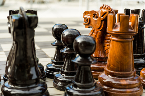 Large street chess figures on board - pawns rook knights