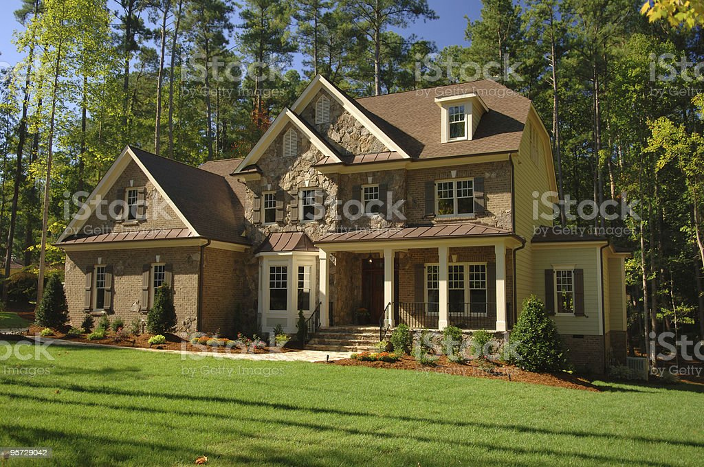 Large suburban home with forest back drop stock photo