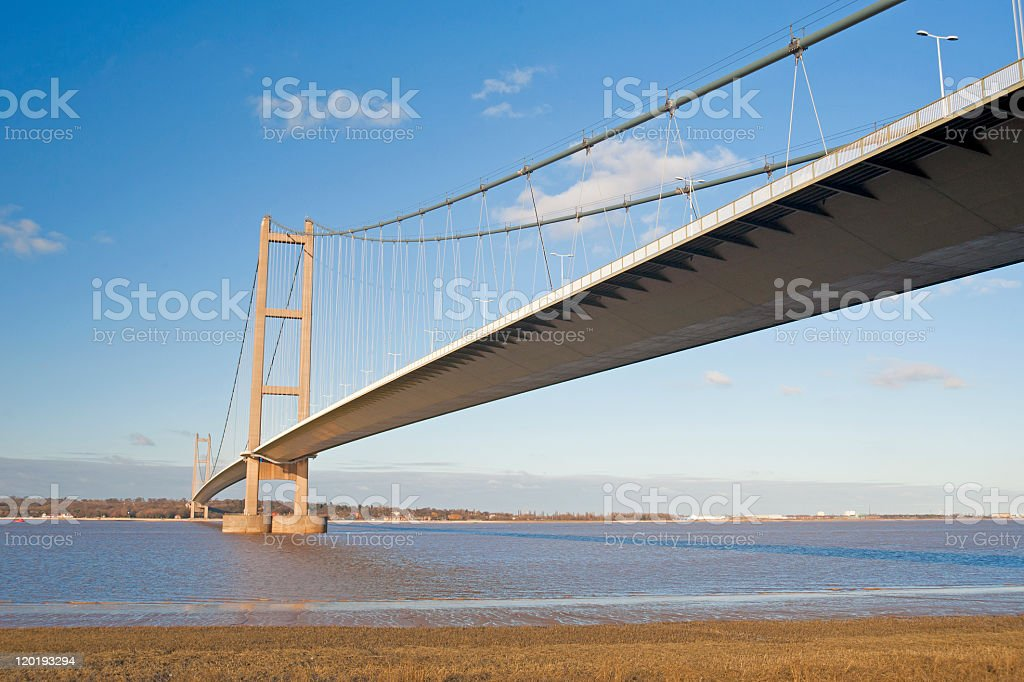 Large suspension bridge over a river during the day stock photo