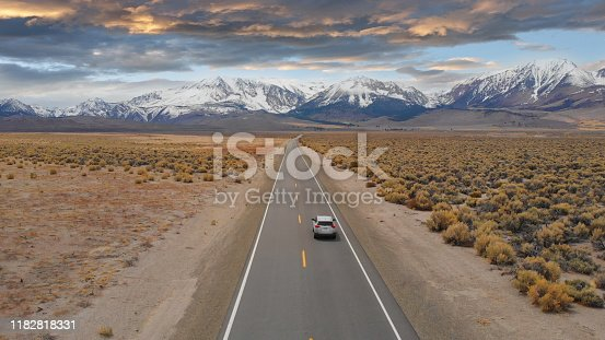 AERIAL: Large SUV drives down the empty highway leading to the spectacular Rockies. Flying above interstate running through the picturesque rugged countryside in Nevada. Breathtaking mountain range.