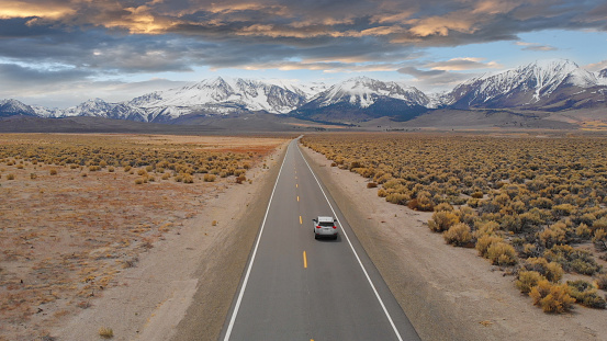 istock AERIAL: Large SUV drives down empty highway leading to the spectacular Rockies. 1182818331