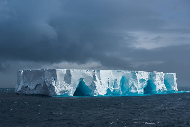 large tabular iceberg floating in antarctica - iceberg stock photos and pictures