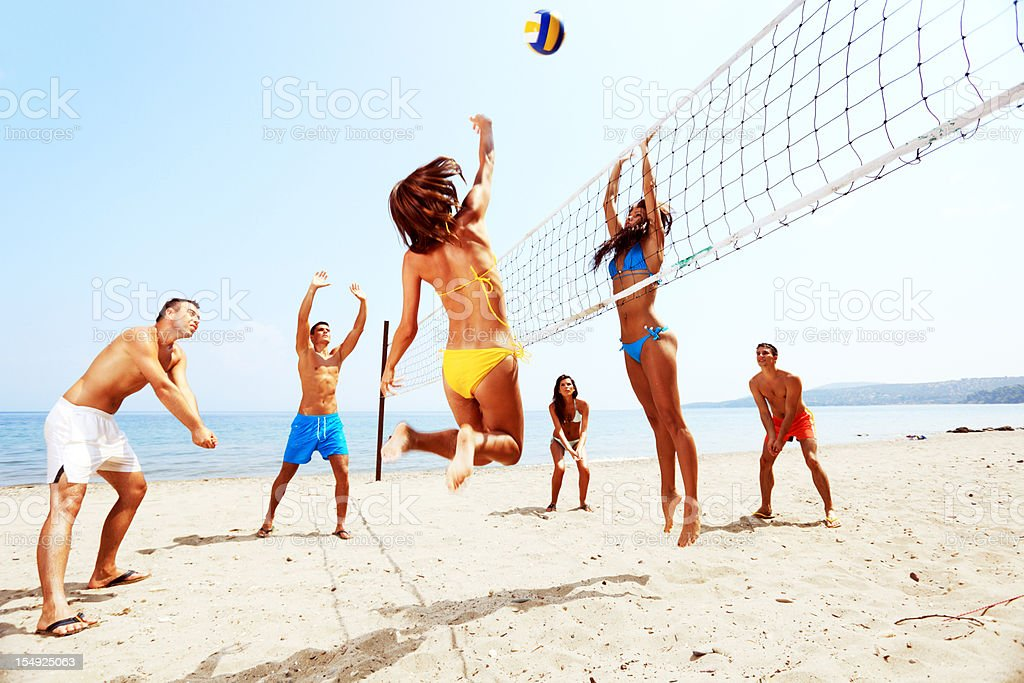 Large team of a people  are playing beach volleyball stock photo