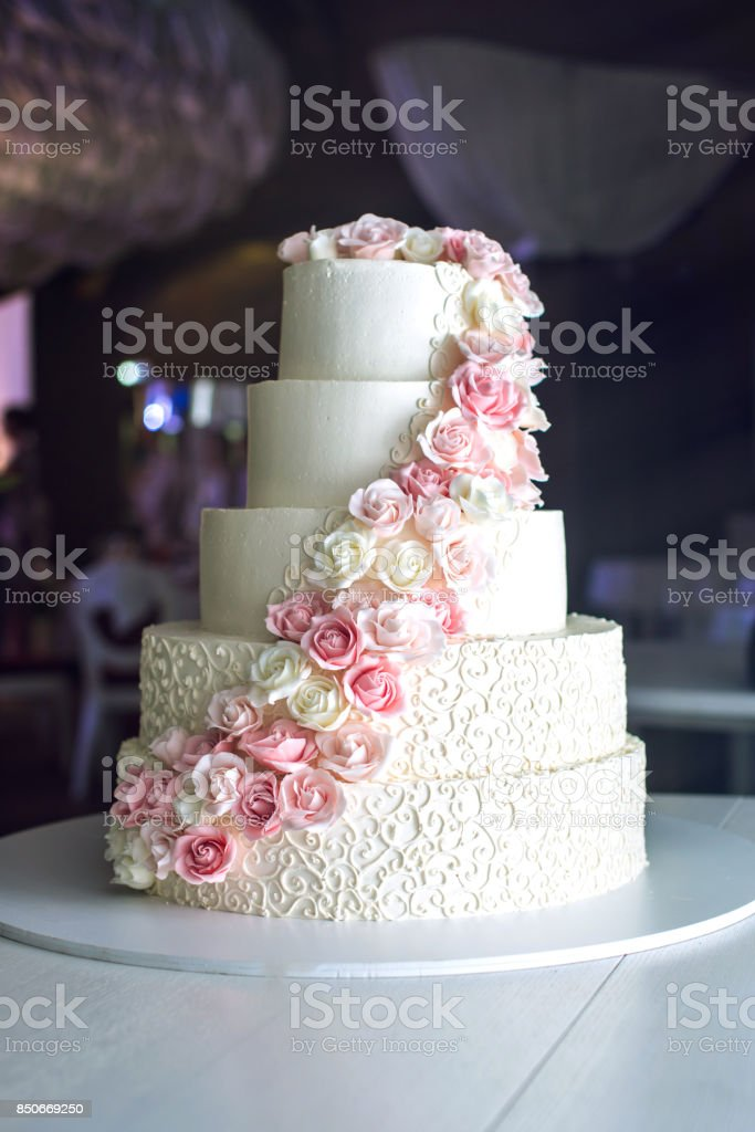 A large tiered wedding cake decorated with pink roses on the table in the restaurant stock photo