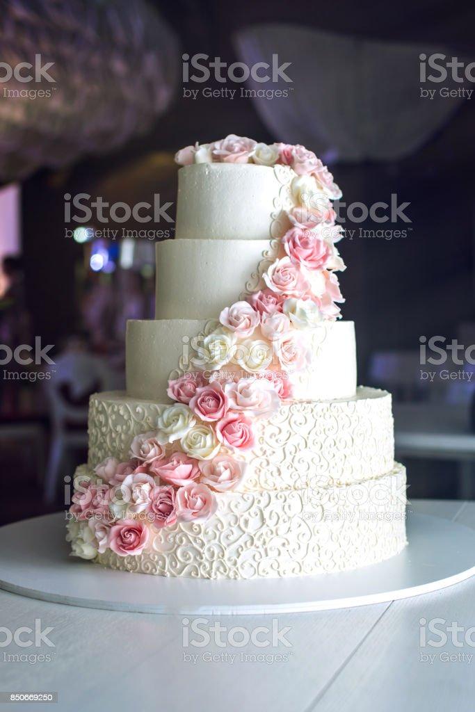 Um grande bolo de casamento hierárquico, decorado com rosas cor de rosa sobre a mesa no restaurante - foto de acervo