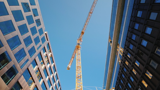 A large tower crane in the downtown of the modern city. Glass office buildings around.