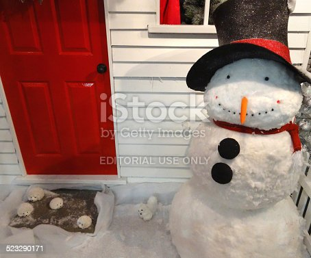 Frome, Somerset, England, UK - November, 9 2014: Photo showing a large cuddly, lifesize toy snowman made from cotton wool, which is part of a seasonal winter Christmas display, outside a 'pretend' red front door / porch.  The cartoon snowman is pictured wearing a scarf and a black top hat, with black coal buttons down its front.  The toy figurine 'statue' is manufactured by 'The Garden Centre Company' and is displayed in a public plaza.