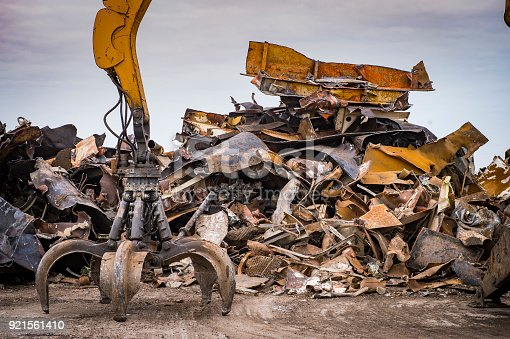istock Large tracked excavator working a steel pile at a metal recycle yard, France 921561410