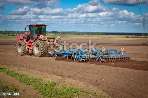Summer scene with heavy ploughing tractor during cultivation agriculture works at field with plough