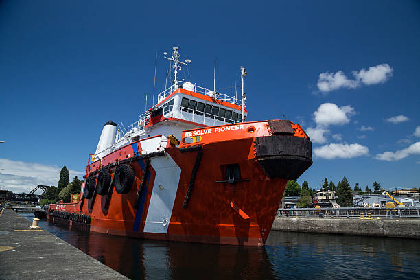 Large tugboat firefighting ship departs main lock at Ballard Locks stock photo
