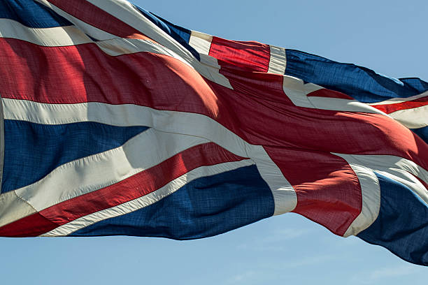 Large Union Jack flying with blue sky stock photo