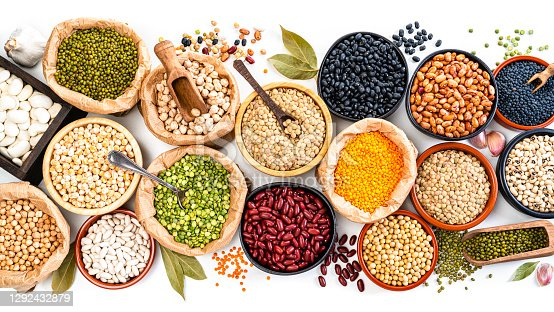 Food Backgrounds: large variety of dried beans, legumes and cereals shot from above on white background. The composition includes green, yellow and brown lentils, chick-peas, black beans, Pinto beans, Kidney beans, fava beans, mung beans, white beans and soy beans among others. High resolution 35,5Mp studio digital capture taken with SONY A7rII and Zeiss Batis 40mm F2.0 CF lens