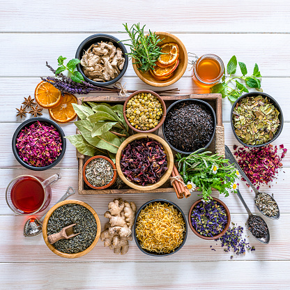 Herbal tea. Large variety of dried herbs and flowers for preparing healthy detox infusions shot from above on white table. The composition includes dried part of plants like hibiscus, calendula, rose petals, chamomile, green tea, bay leaves, cinnamon sticks, ginger, lemons, mint leaves, a honey jar and dried orange slices among others. High resolution 42Mp studio digital capture taken with Sony A7rii and Zeiss Batis 40mm F2.0 CF lens