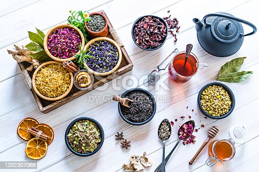 Herbal tea. Large variety of dried herbs and flowers for preparing healthy detox infusions shot from above on white table. The composition includes dried part of plants like hibiscus, calendula, rose petals, chamomile, green tea, bay leaves, cinnamon sticks, ginger, lemons, mint leaves, a honey jar and dried orange slices among others. A tea cup and a black teapot are also included. High resolution 42Mp studio digital capture taken with Sony A7rii and Zeiss Batis 40mm F2.0 CF lens