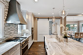 istock Large vent hood and island in kitchen 1276734251