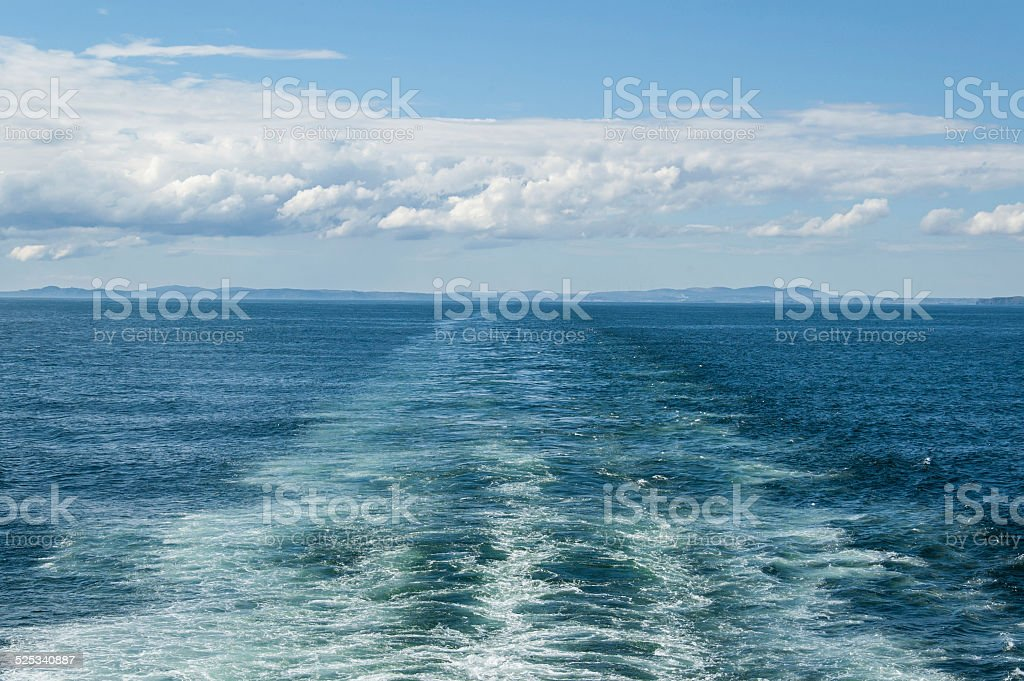 Large wake on blue open ocean left by a large ferry boat