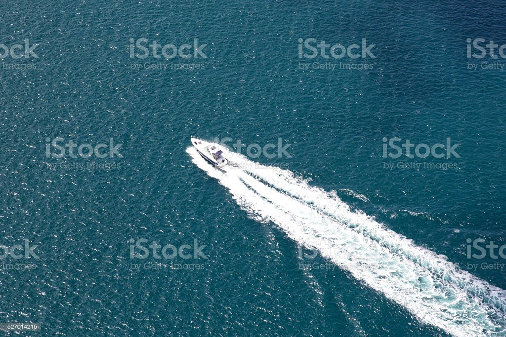 Large wake on blue open ocean left by ferry boat stock photo