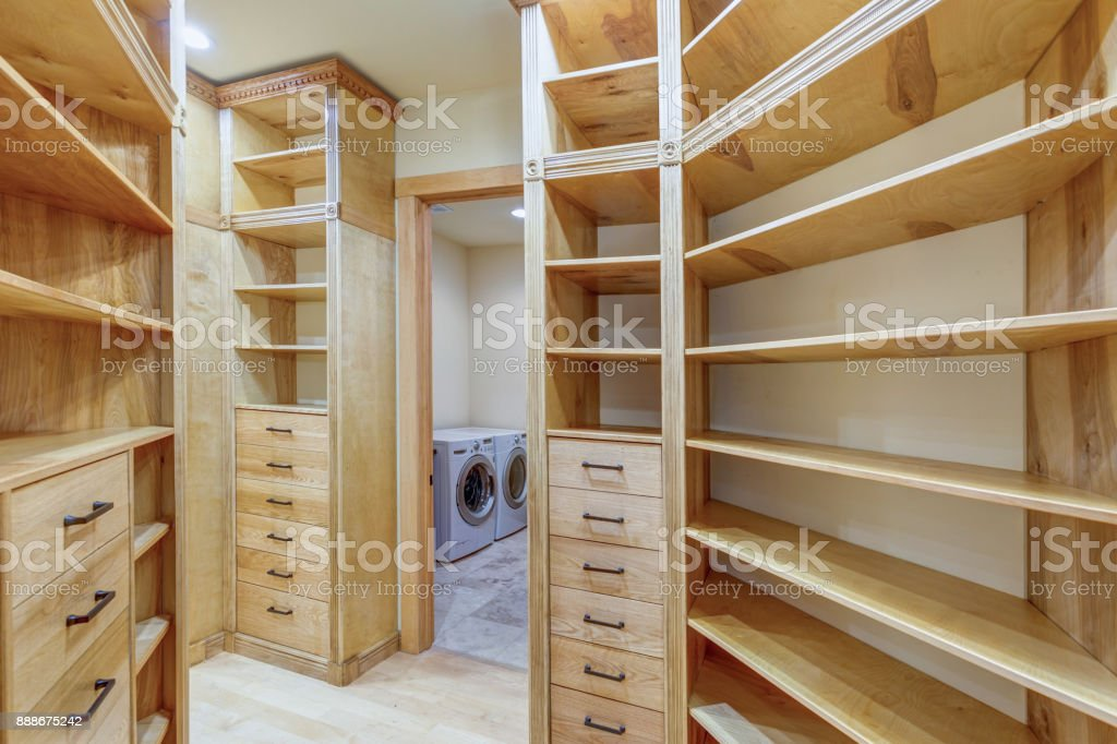 Large walk-in closet lined with built-in drawers stock photo