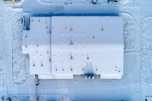 Großer Lagerkomplex, das Dach des Gebäudes ist komplett mit Schnee bedeckt. – Foto