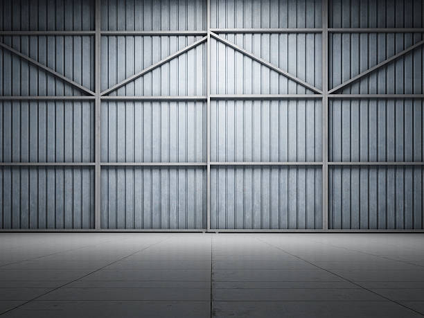 Large warehouse door illuminate Large warehouse door illuminate spot light airplane hangar stock pictures, royalty-free photos & images