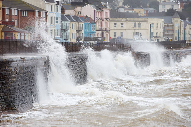 Large waves breaking against the sea wall at Dawlish, Devon Large Waves Breaking Against Sea Wall At Dawlish In Devon coastal feature stock pictures, royalty-free photos & images