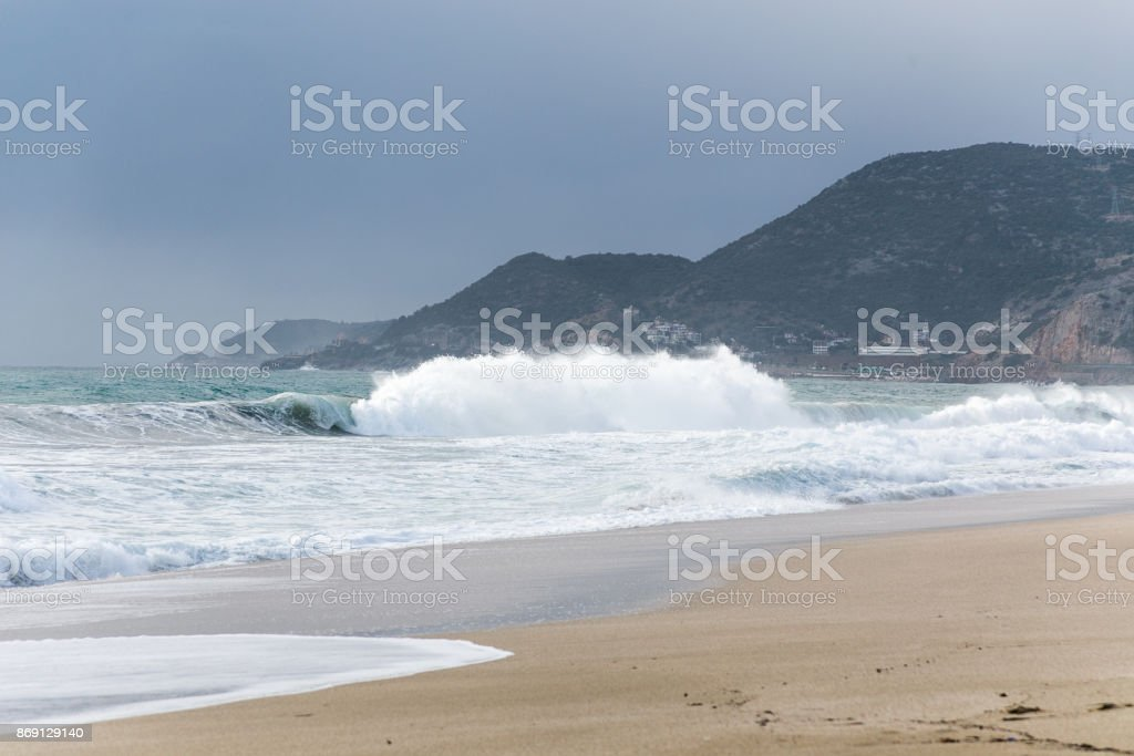 Large waves hitting the shores beach in coastal town stock photo