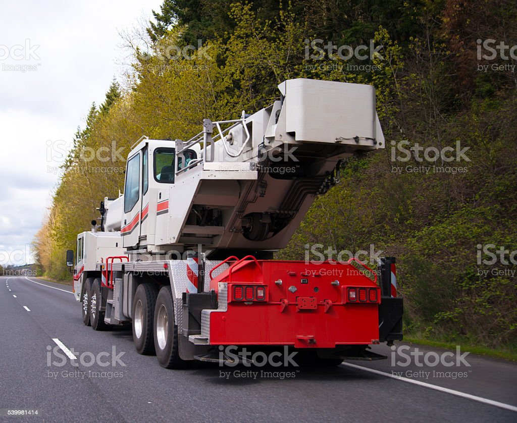 Large wheeled mobile portable crane with extendable boom on road stock photo