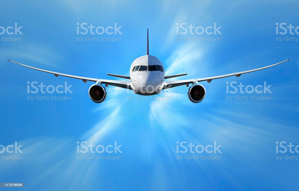 Large white airplane flying towards camera in blue sky stock photo