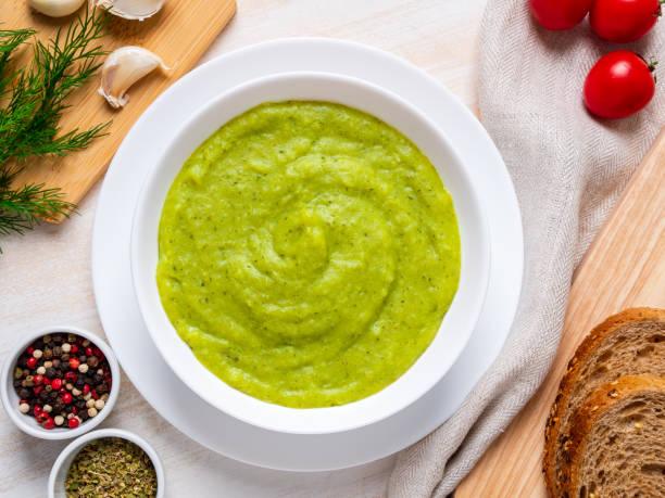große weiße schüssel mit grünen creme gemüsesuppe brokkoli, zucchini, grüne erbsen auf weißem hintergrund, ansicht von oben - schnelle suppen stock-fotos und bilder