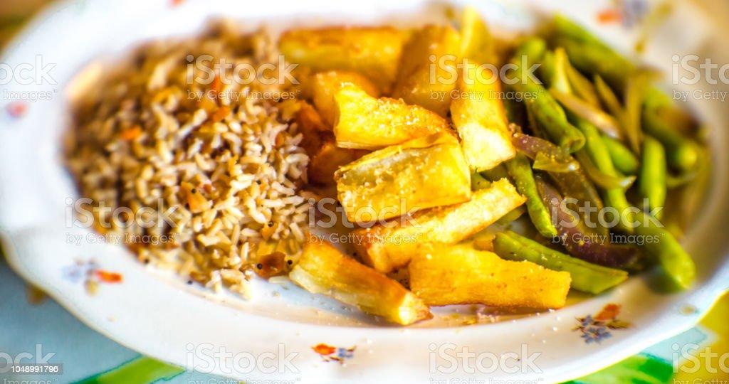Prato branco grande com arroz integral, mandioca e vagem. Foco seletivo. - foto de acervo