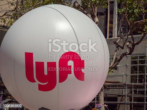 istock Large white Lyft balloon waving in an urban setting 1006383920