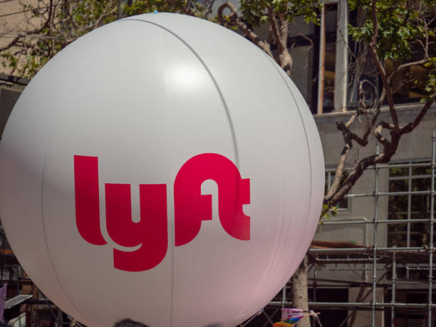 large white lyft balloon waving in an urban setting - rideshare stock photos and pictures