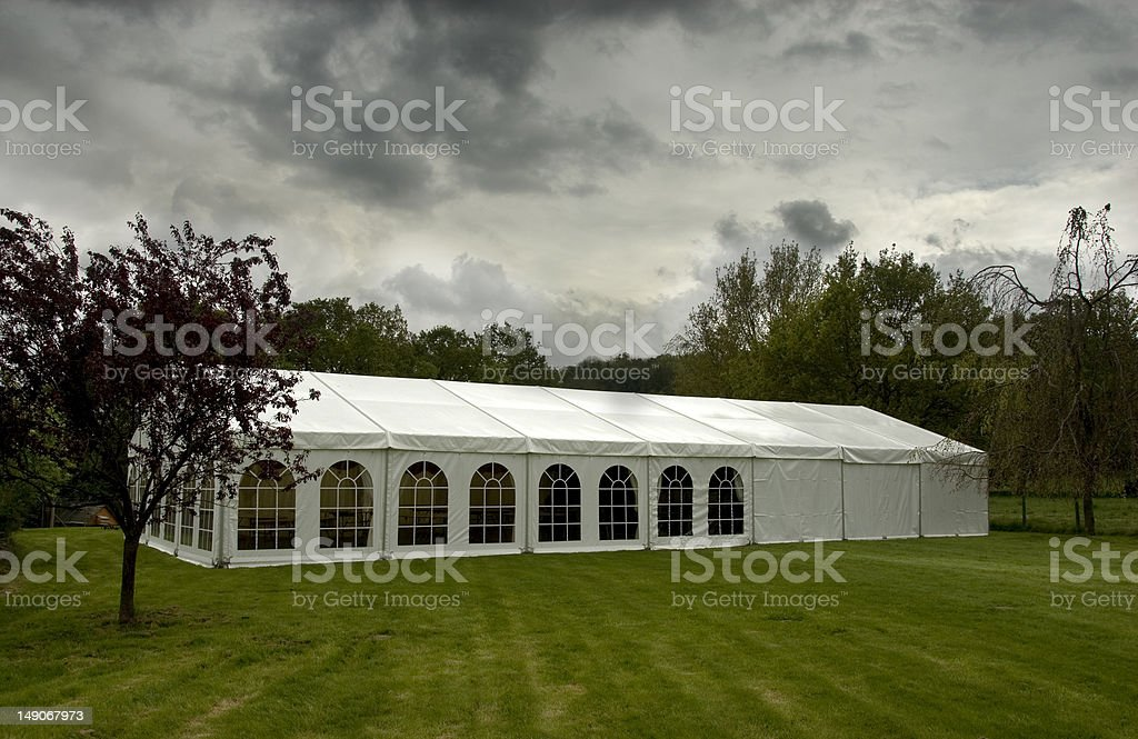 Large white marquee on a green lawn on an overcast day stock photo