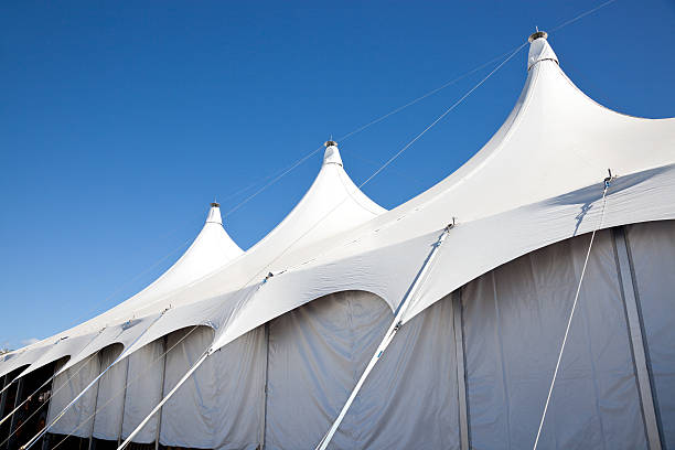 Large White Marquee Tent with clear blue sky Top of a large white event marquee tent for entertainment, party or exhibition. entertainment tent stock pictures, royalty-free photos & images